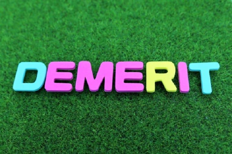 芝生に置かれたデメリットというロゴの文字