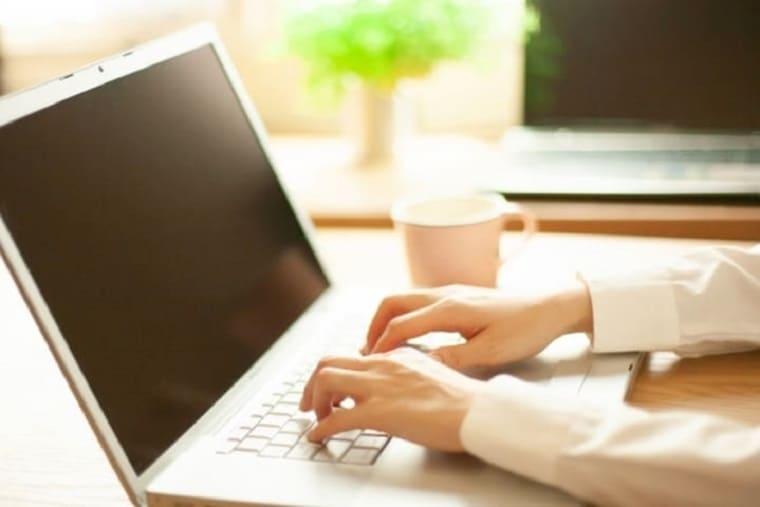 ノートパソコンのキーボードを打っている女性