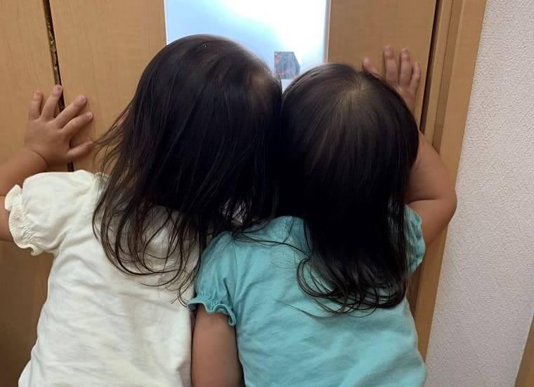 並んでリビングのドアから玄関を見る双子の女の子
