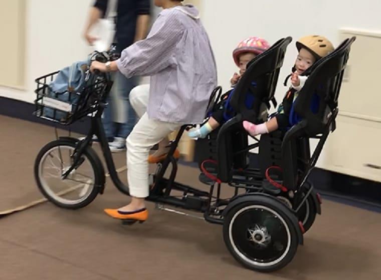ふたごじてんしゃに双子を乗せて運転する女性