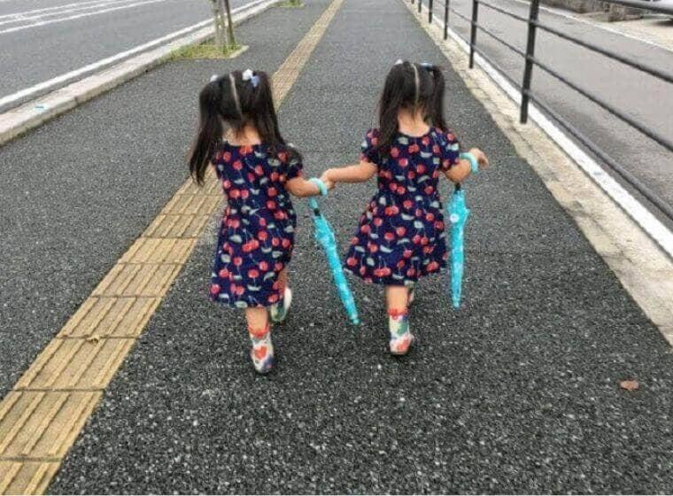 傘を持って手をつなぎながら歩道を歩く女の子の双子