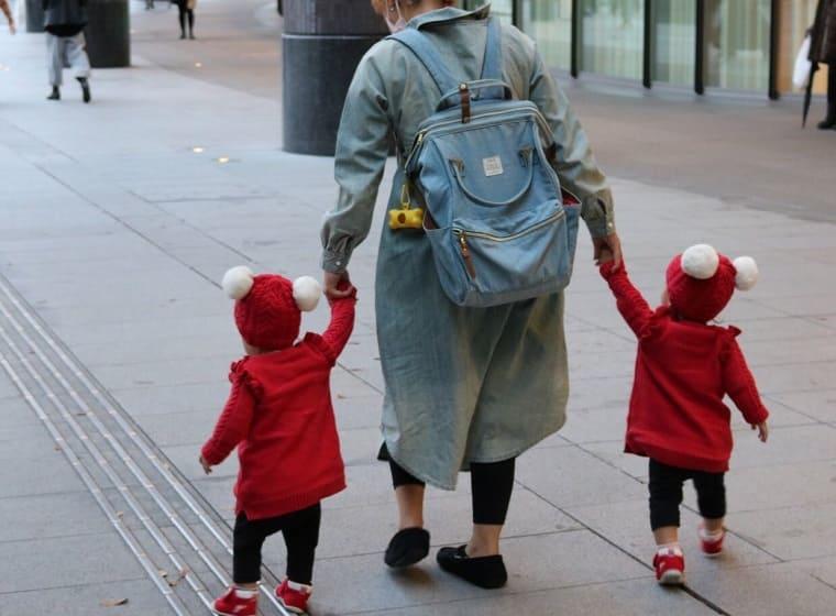 リュックを背負って双子と手をつないで歩く女性