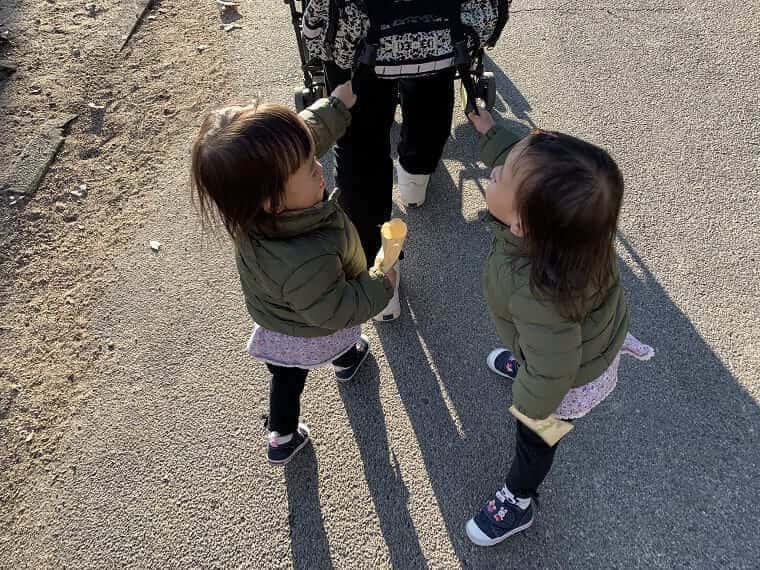2人でふざけあって歩く2歳の双子