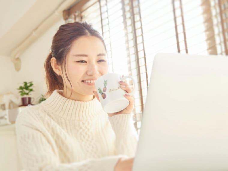 コーヒーを飲みながら笑顔でパソコンをする女性