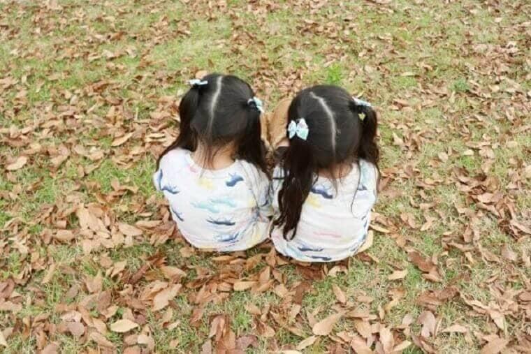 公園で背中を向けて遊ぶ女の子の双子