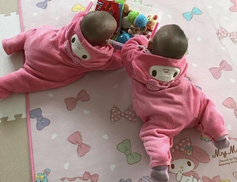 うつ伏せで遊ぶ双子の女の子の赤ちゃん