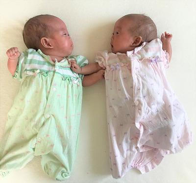 寄り添って寝転ぶ生後5か月の女の子の双子の赤ちゃん