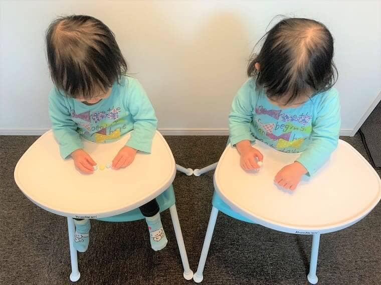 2台のベビービョルンハイチェアにそれぞれ座ってお菓子を食べる双子の女の子