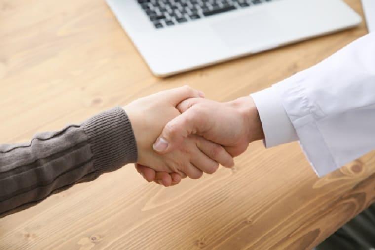 握手をする女性と白衣の医師