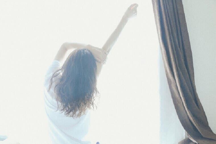 窓の外に向かって背伸びをする女性