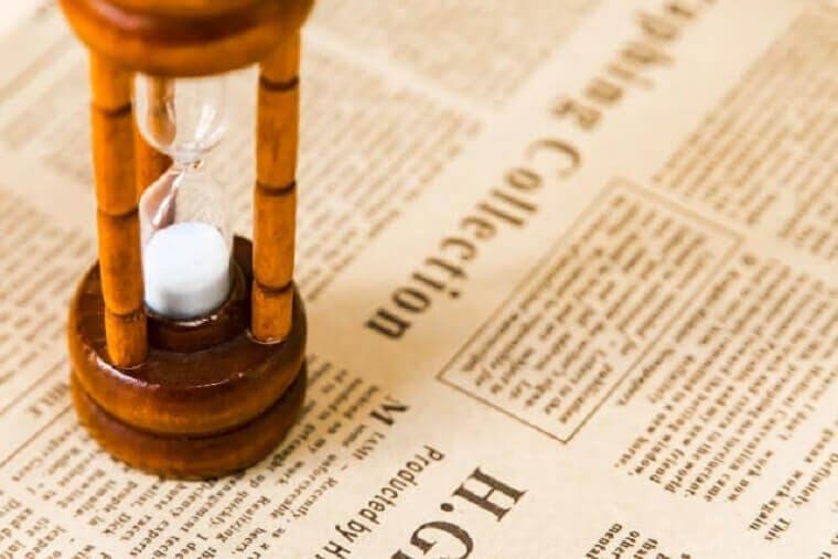 英字新聞の上に置かれた砂時計