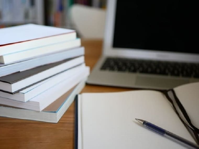 パソコンの前に山積みにされた本