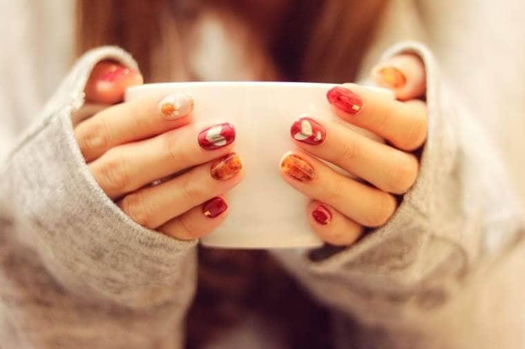 コーヒーカップを両手で持った女性