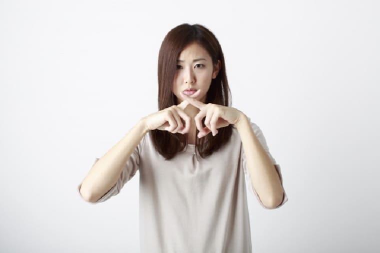 胸の前で指でバツマークをする女性