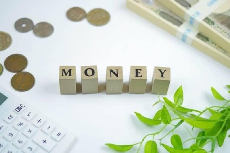 MONEYと書かれた積木と一万円札の束