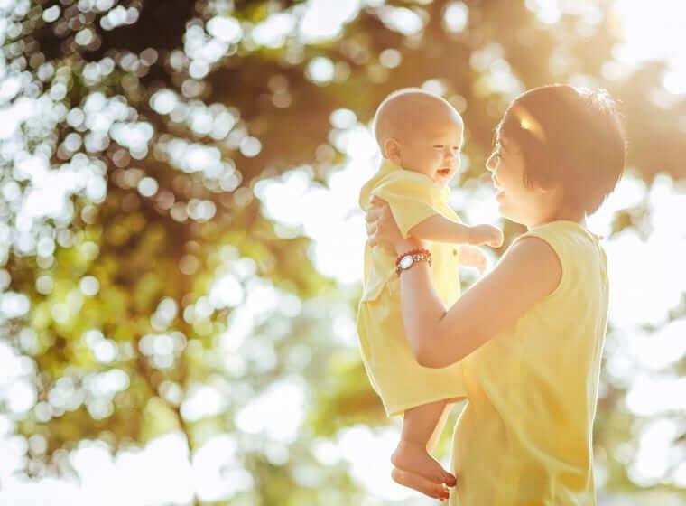 木漏れ日の下で赤ちゃんを抱っこする笑顔の女性