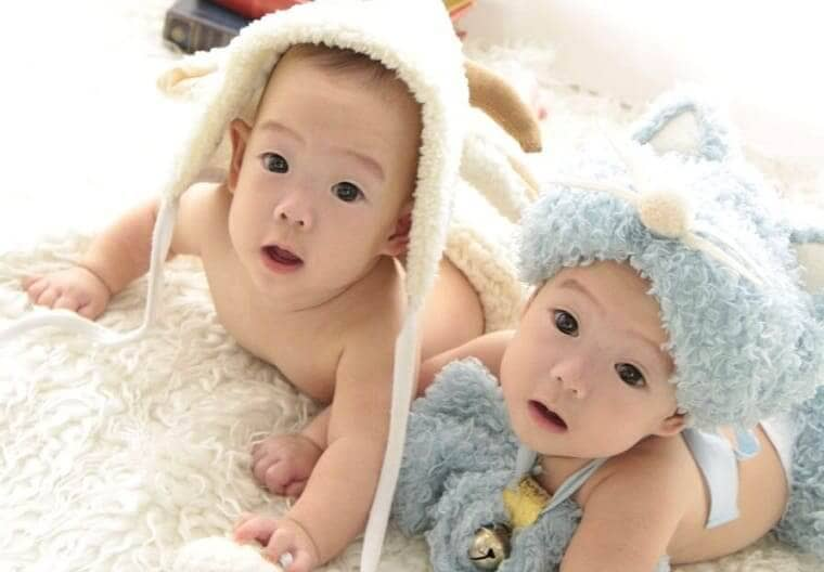 うつ伏せで寝転がる生後6か月の女の子の双子の赤ちゃん