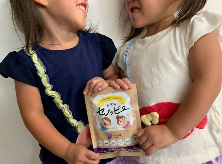 笑顔でセノッピーを持つ3歳双子の女の子