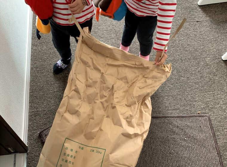 お米の袋を強力してひきずる双子の女の子