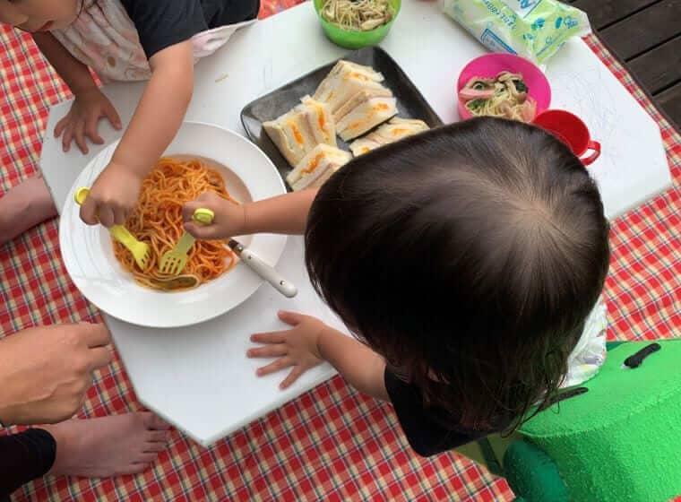 ウッドデッキでお昼ごはんを食べる3歳の双子の女の子