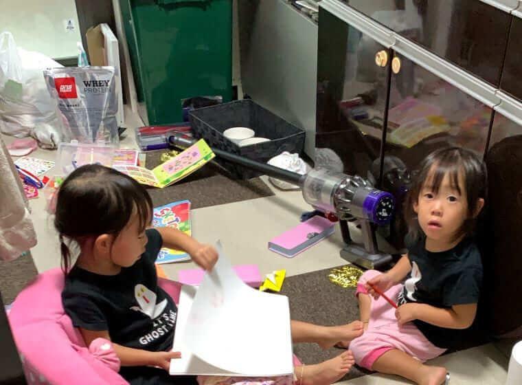 キッチンでおもちゃを広げる3歳の双子の女の子